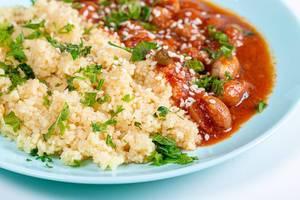Nahaufnahme zeigt Getreide-Couscous mit Sesam, Kräutern und Bohnen in Tomatensauce