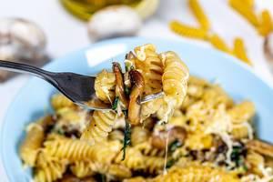 Nahaufnahme zeigt Nudeln auf einer Gabel, mit Pilzen und zerlaufenem, geriebenem Käse