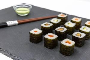 Nahaufname von Moso-Maki Sushi mit Stäbchen und Wasabi Dip im Hintergrund