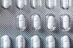 Nahe Aufnahme von oben auf Tablettenpackung mit länglichen weißen Pillen mit medizinischer Wirkung