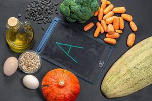 Nahrungsmittel reich an Vitamin A umrunden eine schwarze Kreidetafel in der Mitte