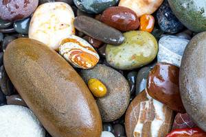 Natural background of wet multicolored sea stones