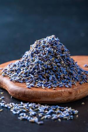 Natural dry lavender flowers tea on wooden board