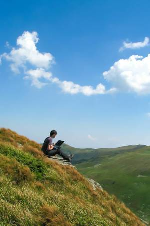 Nature Landscape Photo of Person Working on Laptop in Mountain Area with Blue Sky
