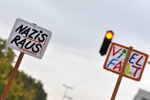 Nazis Raus und Vielfalt Schilder von einer Demonstration vor einer roten Ampel symbolisierend