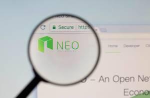 NEO-Logo am PC-Monitor, durch eine Lupe fotografiert