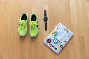Neongelbe Asics Laufschuhe mit Garmin Armbanduhr und Macbook auf Parkettboden