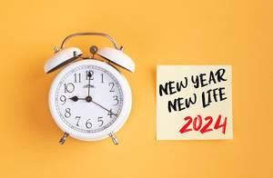 Neue Anfänge: Wecker und ein Zettel mit 'New year - New life 2024' Text vor gelbem Hintergrund