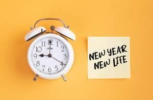 Neue Anfänge: Wecker und ein Zettel mit 'New year - New life' Text vor gelbem Hintergrund