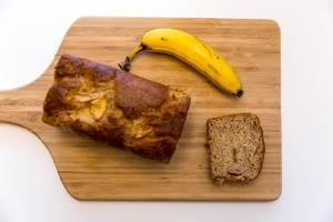 Neue Werte Bananenbrot Apfel und Zimt auf einem Holzschneidebrett top-view