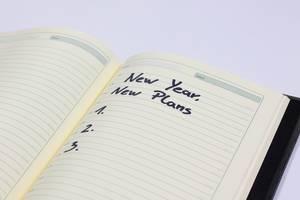 Neues Jahr, Neue Pläne - Neujahrvorsätze auf einem Notizbuch
