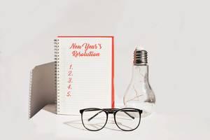 Neujahrs Vorsätze - auf Notizbuch mit Glühbirne und Brille