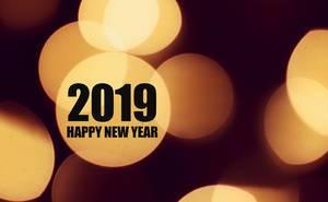 Neujahrsbotschaft 2019 HAPPY NEW YEAR in schwarzen Buchstaben auf hellen Lichtkreisen