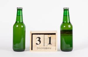 New Year Celebrations with two Bottles of Beer with Wooden Calendar showing December 31 on it on white Background
