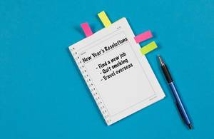 New Years Resolutions - writen on notebook with sticky notes and pen on blue background