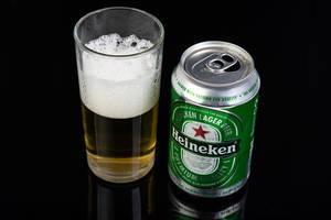 Niederländisches Heineken-Bier aus der offenen Dose, neben einem gefüllten Bierglas, vor schwarzem Hintergrund