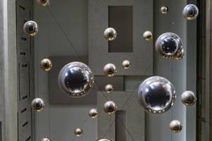 Niedrige WInkelsicht auf glänzende Metalkugeln von Decke hängend