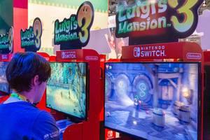 Nintendo Switch Spielstation auf der Gamescom: Spielemesse-Besucher spielen Luigi