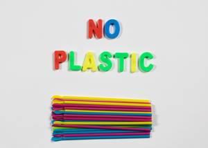 No Plastic Schriftzug mit bunten Trinkhalmen auf weißem Hintergrund