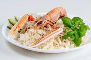 Noodles with fresh basil and lobster on a white background