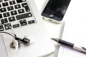 Notebook-Tastatur, Stift, Kopfhörer, Handy und Notizbuch
