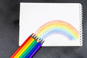 Notebook with painted rainbow and colored pencils on a black background (Flip 2019)