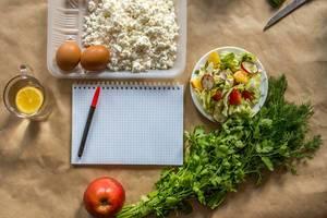Notizblock auf Küchenpapier, zur Erstellung eines Diätplans und Ernährungsumstellung auf gesunde, frische Bio-Lebensmittel