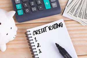Notizbuch mit Text Credit Rating, Sparschwein, Taschenrechner und Dollar Geldscheine auf einem Holztisch