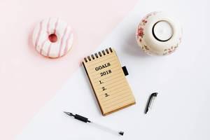 Notizbuch mit Zielen für 2018 auf dem Tisch, aus der Vogelperspektive fotografiert
