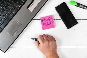 """Notizzettel mit dem Text """"Business Plan?"""" - Geschäftsplan - neben einem Handy und Laptop auf einem weißen Tisch"""