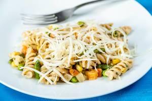 Nudelgericht mit Fusilli-Nudeln und Gemüse auf einem Teller mit geriebenem Käse und Gabel Nahaufnahme