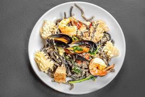Nudeln von oben gesehen - mit Tintenfisch in Cremesauce und Meeresfrüchten