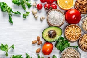 Nüsse, Gemüse und frische Basilikumblätter: gesunde Lebensmittel auf einem weißen Holztisch
