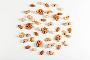 Nuts of different types laid out in the shape of a circle on a white background, top view