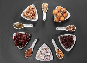 Nuts, seeds, dried dates and candied fruits are arranged in a circle on a black background. Top view (Flip 2019)