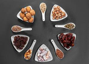 Nuts, seeds, dried dates and candied fruits are arranged in a circle on a black background. Top view