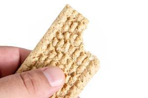 Oat Crackers in the hand above white background