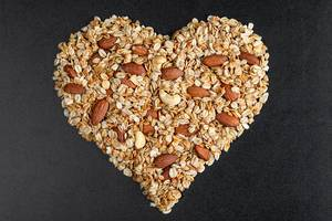 Oatmeal heart with almonds on a black background, top view