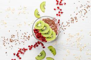Oatmeal porridge with flax seeds, kiwi pieces and pomegranate. Top view (Flip 2019)