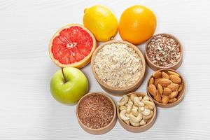 Oatmeal surrounded by nuts and seeds with fresh fruit on a white wooden background. Top view (Flip 2019)