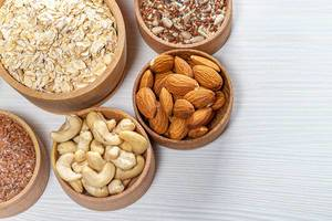 Oatmeal with almonds, cashews, flax seeds and sunflower seeds on a white wooden background. Top view (Flip 2019)