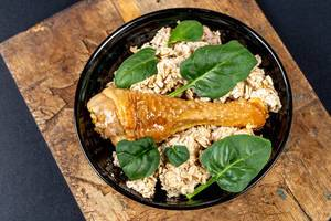 Oatmeal with baked chicken leg and green leaves on an old wooden kitchen board, top view (Flip 2020)