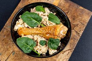 Oatmeal with baked chicken leg and green leaves on an old wooden kitchen board, top view
