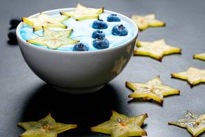 Oatmeal with carambola and blueberries in a white bowl on a black background with sliced carambola pieces (Flip 2019)
