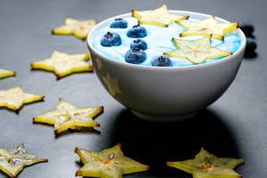 Oatmeal with carambola and blueberries in a white bowl on a black background with sliced carambola pieces