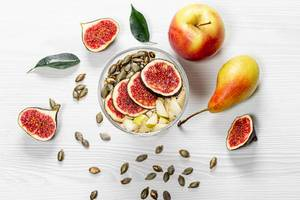 Oatmeal with figs, pears, apples and pumpkin seeds. Top view (Flip 2019)