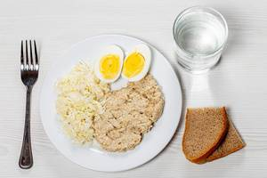 Oatmeal with fresh cabbage salad and boiled eggs on a white table with black bread and a glass of water (Flip 2019)