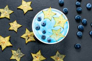 Oatmeal with fresh carambola and blueberry berries on black background. Top view