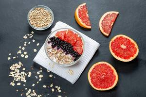 Oatmeal with grapefruit, black elderberry and sunflower seeds on a black background. Top view (Flip 2019)