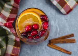 Obene Aufnahme von einem Glass Apfelwein mit Orangenscheiben, Preiselbeeren und Zimtstangen